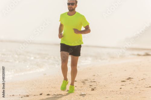 Fotobehang Hardlopen Jogging on a tropical sandy beach near sea / ocean.