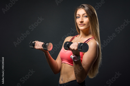 Poster beautiful athletic young woman with muscles doing exercises with dumbbells bodybuilding