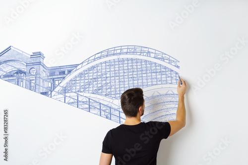 Fridge magnet mann zeichnet eine bauzeichnung an eine weiße wand