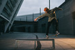 young skateboarder balancing with board on bench