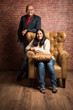portrait of senior indian couple while sitting on sofa of wing chair