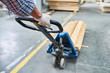 Closeup of unrecognizable man pulling moving cart with wooden  boards in warehouse of modern factory, copy space