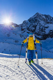 Mountaineer backcountry ski resting along a snowy ridge with skis in the backpack. In background blue sky and shiny sun and Ortler in South Tirol, Italy.  Adventure winter extreme sport. - 183300419