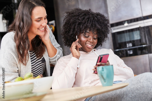 Fototapeta Zwei junge Frauen hören Musik mit Smartphone