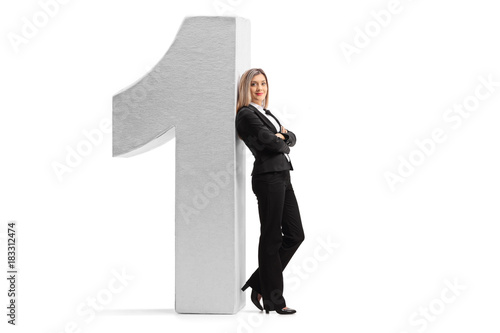 Formally dressed woman leaning against a cardboard number one Poster