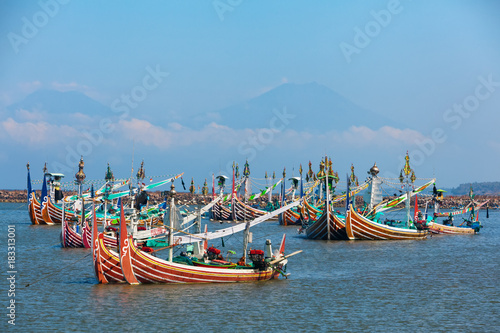 Staande foto Bali Traditional wooden fishing boats in Bugis style mooring in old fishers port on Bali island near Perancak village. Popular place to visit in Jembrana regency. Indonesia travel and culture background.