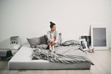 Girl sitting on bed in the morning - 183315087