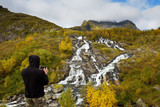 Tourist photographing Lofoten waterfall with a mobile phone in Norway