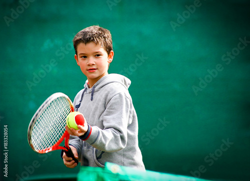 Little tennis player on a blurred green background.
