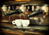 Coffee maker pours hot coffee into two white cups - 183330874