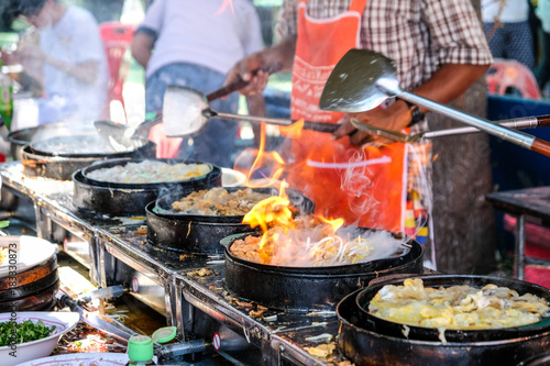Sticker Fried mussel pancakes with egg are cooking on the pan with smoke and fire