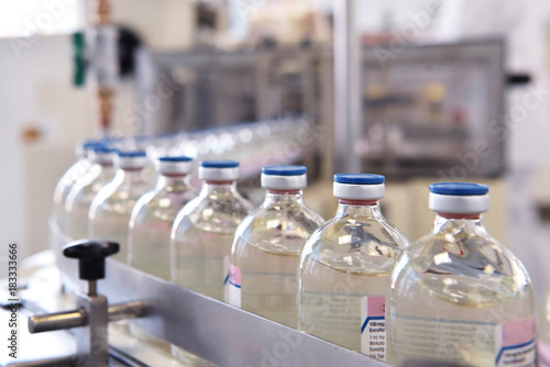 Fotobehang Apotheek Produktion von Medikamenten - fliessband mit Arzneimittel in Glasflaschen auf einem Fliessband in der Pharmaindustrie