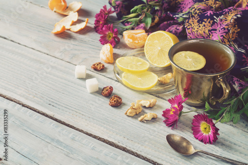 Cup of tea, lemon and flowers on a white wooden table