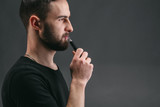 Young man vaping e-cigarette with smoke on black - 183336003