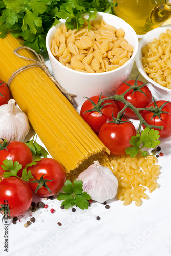 Poster spaghetti, tomatoes and fresh ingredients on a white table, vertical top view