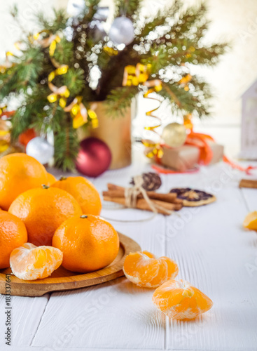 Christmas concept with Tangerines, Fir branches with decor , gifts and spices on the white wooden table. New year background. Selective focus. Space for text - 183337641