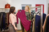 stylist helping chooses dress for the customer - 183340298