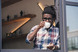 african american man drinking coffee in cafe - 183340679