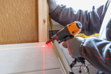 The worker makes finishing works of walls with a white wooden board, using laser line level. Building heat-insulating eco-wooden frame house with wood fiber plates - 183345674