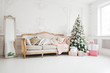 New Year's holiday or celebration, the mood, Stylish Christmas minimalistic interior, Presents and wrapped gifts under the Christmas tree. large white living room with a vintage sofa