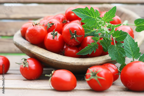 Fotobehang Kersen Fresh tomato crop in a wooden bowl