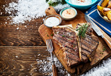 Grilled t-bone steak with sauces and side dishes