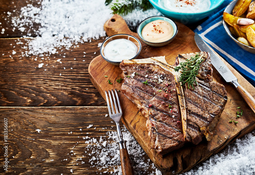 Foto op Canvas Steakhouse Grilled t-bone steak with sauces and side dishes