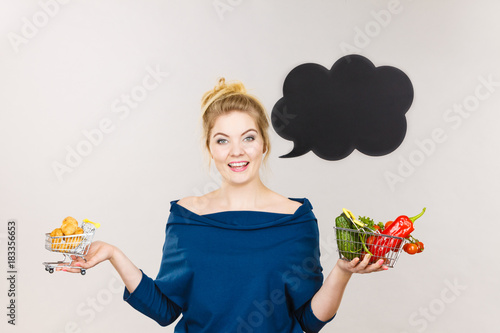 Woman holding basket with fruits and sweet bun