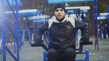 Tilt up of Young athlete man doing exercise at outdoor gym in winter park - 183358046