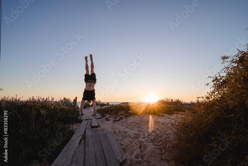 Foto op Canvas Chocoladebruin Man doing handstands at sunset in Portugal