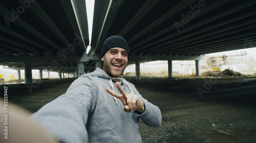 Staande foto Jogging POV of Happy sportive man taking selfie portrait with smartphone after training in urban outdoors location in winter
