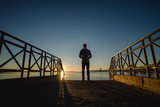 Man watching the sunrise from a bridge in Portugal