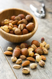 Assorted mixed nuts in bowl on wooden table - 183361636