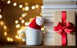 white cup with Christmas hat and books