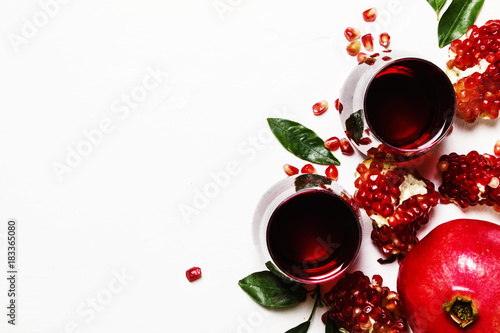 Pomegranate juice in glass on white stone background, top view