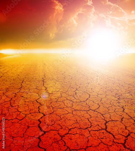 Plexiglas Rood traf. dramatic sunset over cracked earth