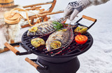 Two whole fish grilling over a winter barbecue