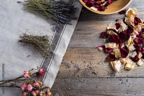 Collected herbs and rose petals, lying on a linen napkin