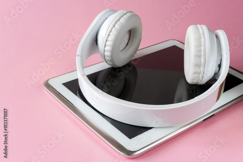 Headphones white tablet on a pink background with copy space top view