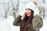 Beautiful young girl outdoors in the snow wearing hood - 183374686