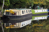 barges converted into houseboats moored on a canal near hebden bridge in yorkshire in woodland - 183378401