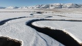 Aerial shot of a winding river running through a snow covered landscape - 183389624