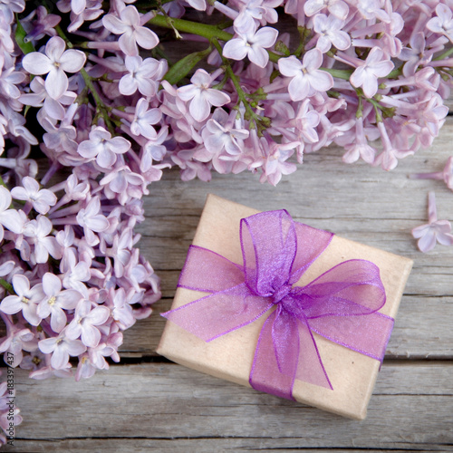 Foto op Canvas Lilac Gift box with purple bow and lilac on wood