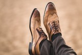 Cropped image of male brown shoes on men - 183400693