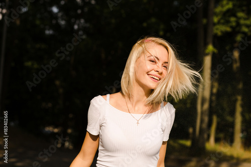 Happy blonde woman in white t shirt with hair in motion posing in the park