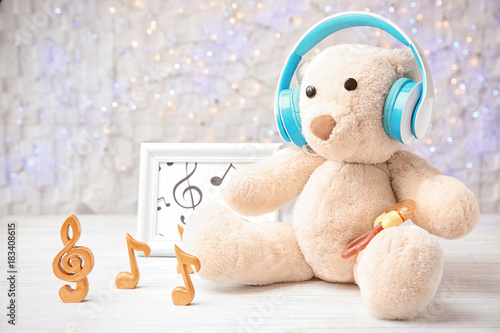Toy with headphones on table against color wall. Baby songs concept