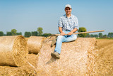 Smiling farmer sitting on hay in his field - 183410607