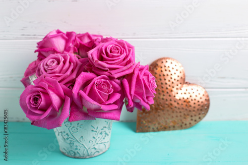 Pink roses flowers and heart on turquoise wooden background against white wall.