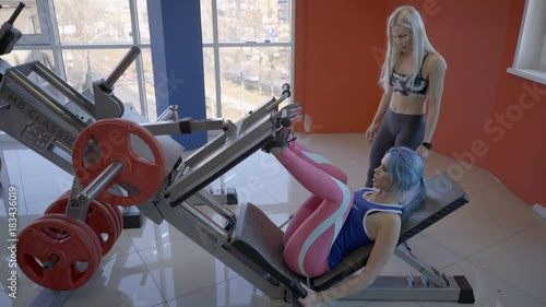 Sticker The young woman does weight leg presses in the luxury gym with a trainer. The sportswoman lies on the inclined bench during the exercises for glutes and her female blond couch stands near and helps