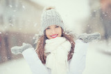 Beautiful smiling young woman in warm clothing. The concept of portrait in winter snowy weather - 183450648